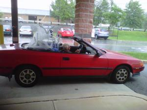 red convertible, raining, caught in the rain, top down, lawn furniture