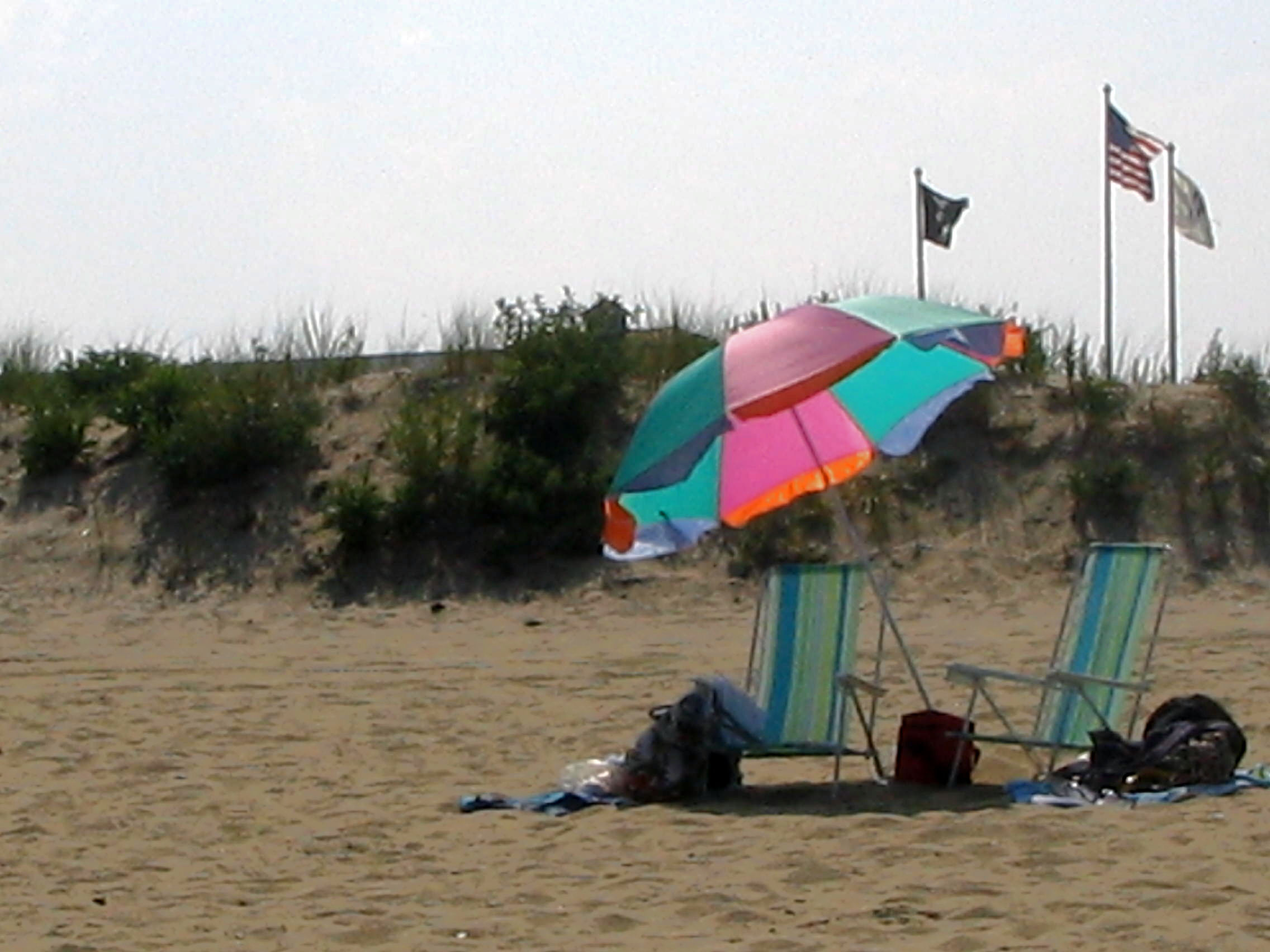 beach umbrella two empty chairs