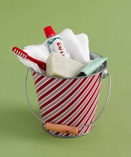 bathroom neccessities, striped pail, toothpaste, toothbrush, washcloth