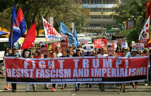 Filipino activists hold banner and placards while marching towards the U.S. embassy during a protest against U.S. President Donald Trump's immigration policies, in metro Manila